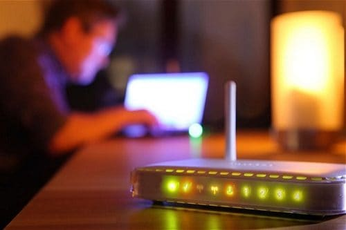 Router with Lights Glowing and a Person On a Computer in the background